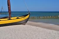 Apartamenty.in | żółta łódka na brzegu morza w Chałupach